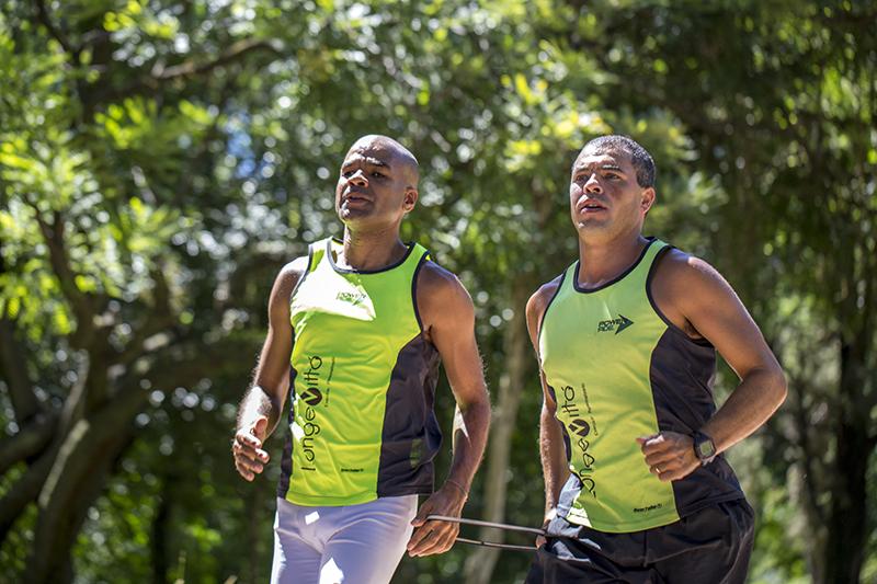 Dois homens aparecem na foto. Alexandre está à esquerda, correndo junto com o seu treinados Eduardo Peres.