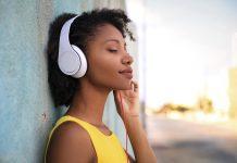 música na corrida - Mulher usando fones de ouvido enquanto está encostada na parede