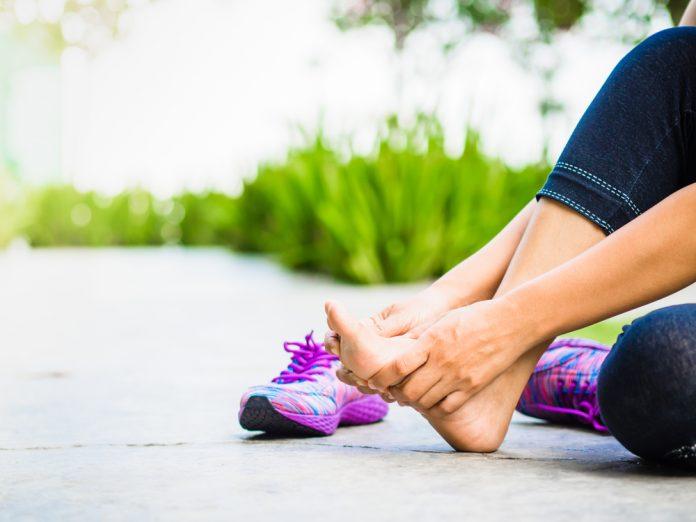 fortalecimento dos pés: mulher massageia o pé com as mãos