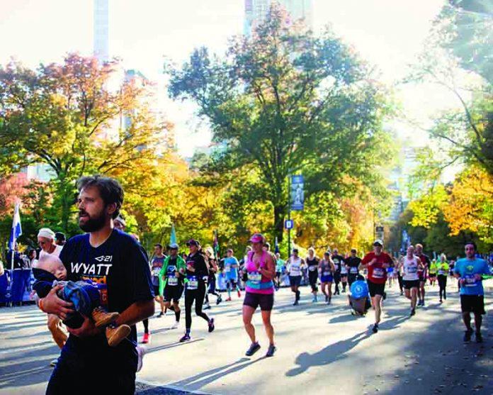 Pai de criança com síndrome de Down termina maratona com filho no colo
